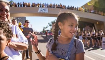 girl making pitchfork sign with hand at ASU Homecoming parade
