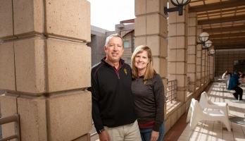 ASU alum husband and wife smiling in the hallway of a campus building