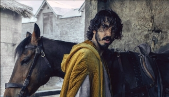 Actor Dev Patel stands in front of a horse and looks over his shoulder in a photo still from the film