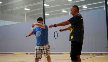 person being taught out to serve a badminton shuttlecock