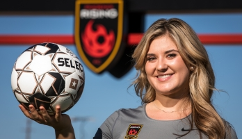 woman holding soccer ball smiling