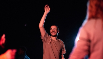 man with one arm raised standing in the middle of a crowd