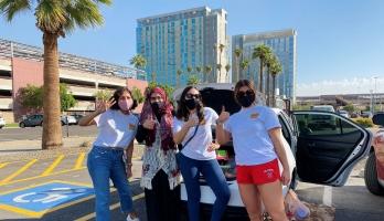 group of ASU student volunteers make the Pitchfork sign