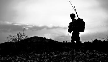 black and white photo of landscape with a soldier silhouetted in the foreground