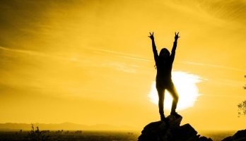 woman on mountain with sun behind her making pitchforks with hands