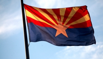 Arizona State flag with a blue sky in the background