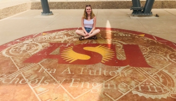 Incoming engineering first-year student Emily Hagood poses on a sidewalk with the ASU engineering school logo