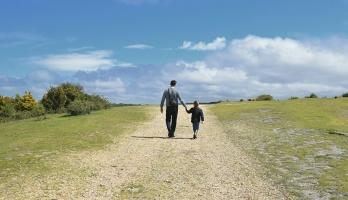 man and child walking along a path
