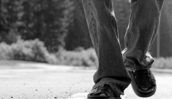 A closeup of someone's feet walking down a road.