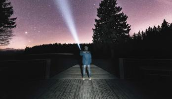 photo of man shining flashlight at starry sky