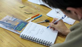 A Lower Mekong Initiative Young Scientist Program participant writes in a notebook.