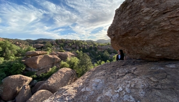 A woman looks out at a landscape while standing against several massive boulders