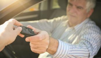 An older man hands his car keys to someone.
