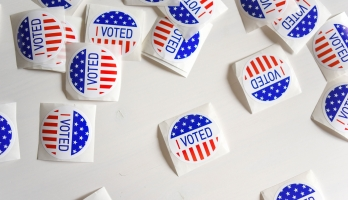 Vote stickers scattered on a white surface
