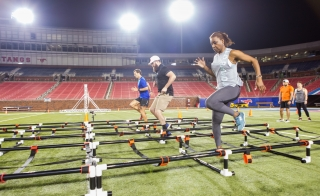 people running through an obstacle course in a stadium