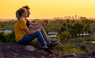 Two people sit on a rock and watch the sunset