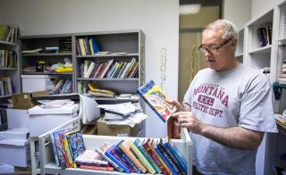 professor holds a book in office full of books