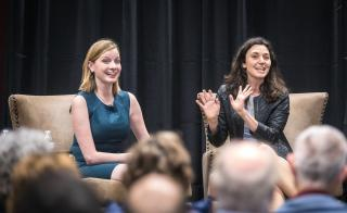 The Pollsters podcast hosts Kristen Soltis Anderson and Margie Omero speak on stage at an event