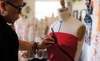 Designer Loren Aragon works on a dress on a dressmaker mannequin