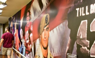 Picture of two people walking down a hallway with Pat Tillman graphics on one wall.