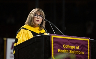 ASU College of Health Solutions Dean Deborah Helitzer speaks at a lectern at the May 2019 commencement