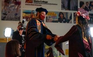 Dean Jonathan Koppell congratulates a spring 2021 Watts College graduate