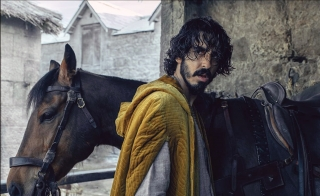 """Actor Dev Patel stands in front of a horse and looks over his shoulder in a photo still from the film """"The Green Knight"""""""