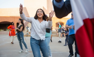 A woman waves her hands and smiles while dancing in a museum courtyard