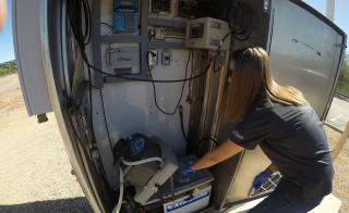 ASU PhD candidate Erin M. Driver examines a water sampling station