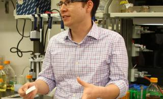 Alexander Green holds a paper-based diagnostic test for the Zika virus