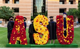 ASU West faculty members in commencement regalia and masks pose next to a flower arrangement that spells out 'ASU' on Fletcher Lawn