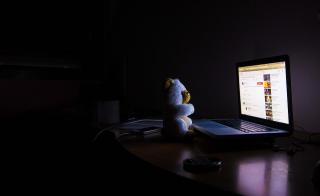stuffed bear looking at bright computer screen in dark room