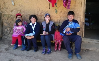 group of people sitting outside a mud brick home in Peru