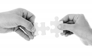 two hands holding two puzzle peices that fit together