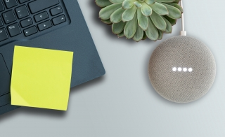 An overhead shot of a laptop with a post it note, a plant and a Google speaker
