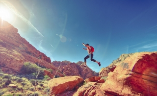 hiker jumping from rock to rock