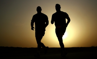 silhouettes of two people running