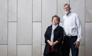 Man and woman posing against wall