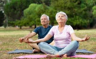 An older adult male and an older adult female meditating while seated on yoga mats in a field.