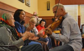 man playing violin to elderly woman