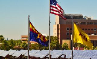 Rooftop solar panels on the ASU Tempe campus are in the background of a three flags: The Arizona state flag, the United States flag and the ASU flag.