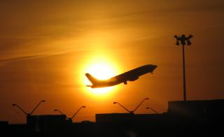 A plane takes off against the sunset