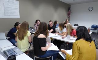 Picture of students around a table discussing a class topic