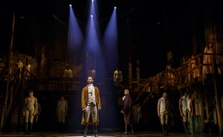 The cast of the Broadway musical Hamilton stands onstage.