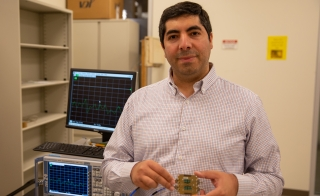 Saeed Zeinolabedinzadeh poses with an integrated circuit developed in his Millimeter-Wave, Terahertz and Photonic Integrated Circuits Lab.