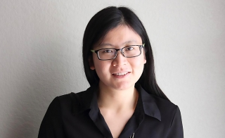 Fengxiu Zhang, a female with long dark hair and black-rimmed glasses faces the camera, smiling in a dark top