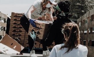 woman wearing a mask, unloading food from a truck