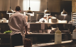 A crew works in a restaurant kitchen