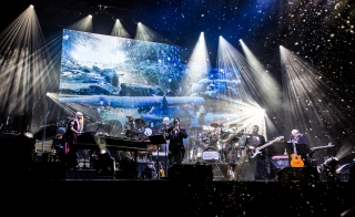 The ensemble of Mannheim Steamroller Christmas performs onstage with an image of snowy mountains behind them and lights imitating snowfall.