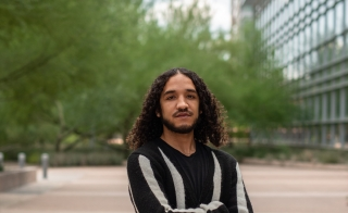 ASU graduate student Dylan Peay stands with arms crossed in the middle of a mall on the Tempe campus